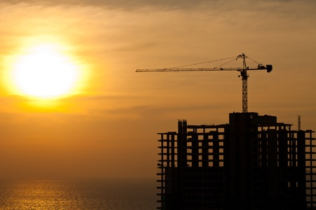construction crane: Industrial construction cranes and building silhouettes with  sunrise