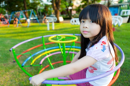 playground equipment: Cute little girl enjoys playing in a children