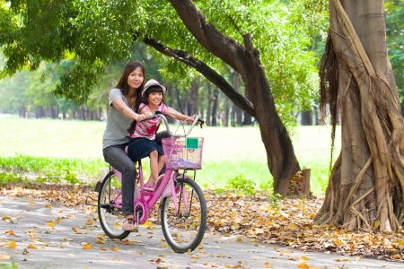 Mother and a daughter cycling bicycle at the park photo