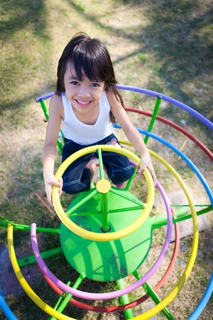 playgrounds: Cute little girl enjoys playing in a children