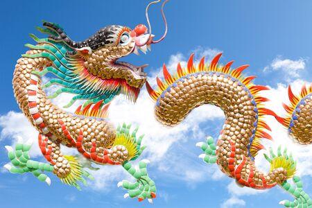 flying dragon: Dragon flying on a fluffy cloud across a blue sky