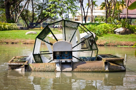 water wheel: Water Turbine a water wheel floating on the pond in a park.
