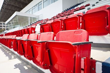 grandstand: Rows of folded, red, plastic seats in very big, empty stadium