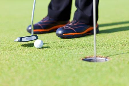 putter: Golf green hole course man putting ball inside short putt Stock Photo