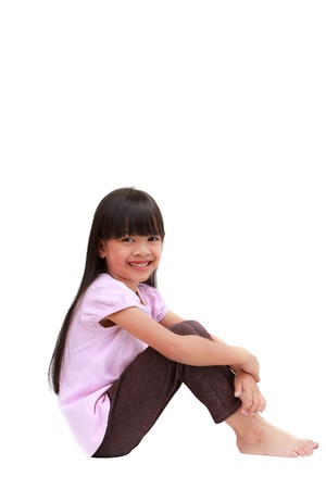 Smile little girl sitting, Isolated on white photo