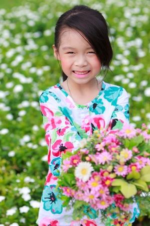 Smiling little girl on the flower filed Stock Photo - 12427933
