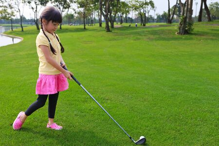 Little girl just swing golf ball on golf course fairway photo