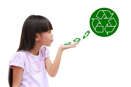 Little girl holding and blowing recycle symbol isolated on white photo