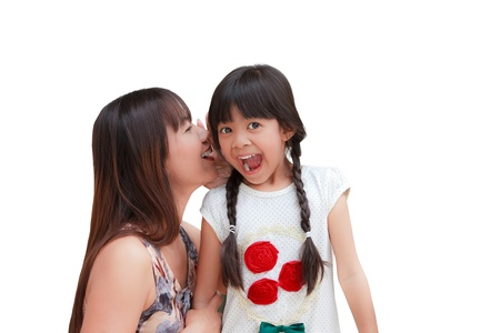 telling: Mother whispering secrets in her daugther Stock Photo