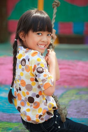 columpios: Niña asiática le gusta jugar en un parque infantil