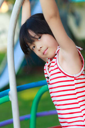 Cute little girl playing in a children playground photo