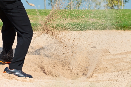 A professional golfer playing a shot out of a sand-trap photo