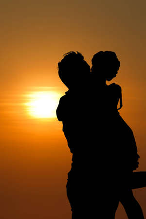 man s: Sunset silhouette a young couple embracing