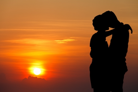 シルエットのカップルが夕日を背景にキス