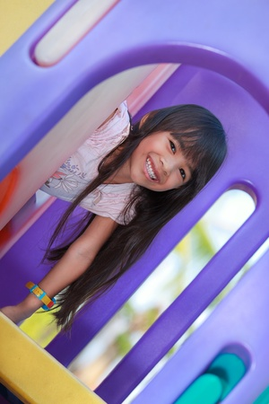 Little girl enjoys playing in a children playground photo