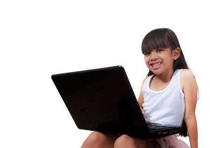 Smiling little girl is sitting with her laptop Stock Photo - 12751410