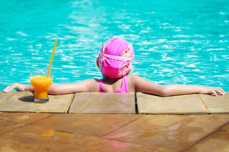 Little girl at swimming pool with orange juice photo
