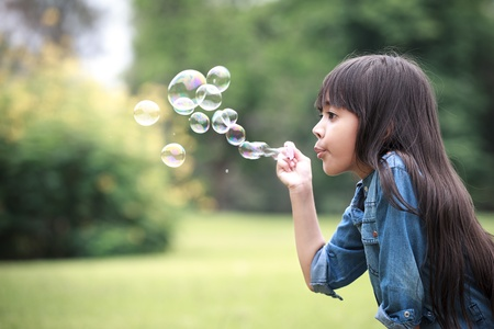 Asian little girl is blowing a soap bubbles Stock Photo - 12927042