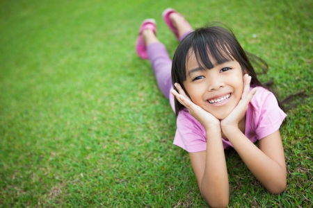 Portrait of a smiling little girl, lying on green grass