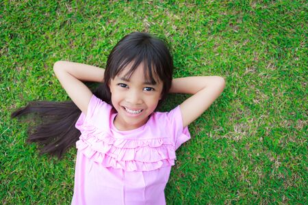 Portrait of a smiling little girl, lying on green grass photo