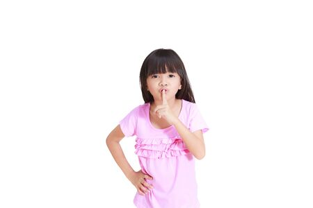Little girl gesturing for quiet or shushing Isolated on white Stock Photo