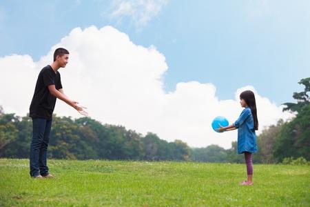 asia family: Hermano y hermana jugando pelota en el parque