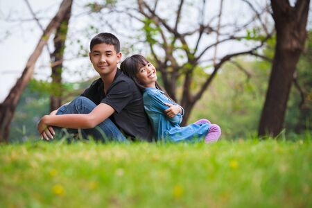 Brother and sister are sitting on the grass in the park photo