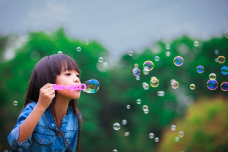 by blowing: Asian little girl is blowing a soap bubbles