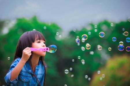 burbujas de jabon: Ni�a asi�tica est� soplando pompas de jab�n a Foto de archivo