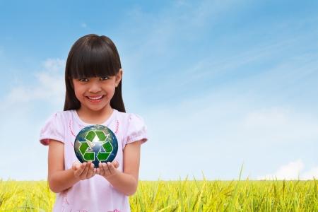 niños reciclando: Niña sonriente sosteniendo la tierra con el símbolo de reciclaje