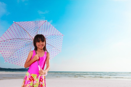Smiling little girl at beach with pink umbrella photo