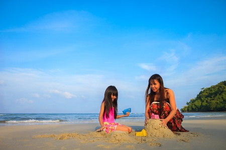 Mother with children playing with sand on beach with blue sky photo