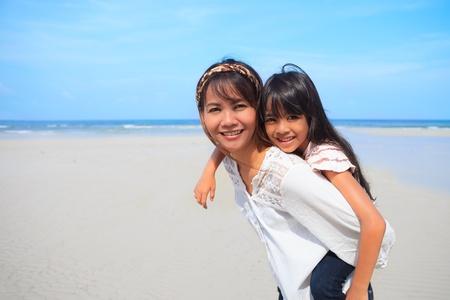 Moeder met dochter een piggyback op het strand Stockfoto