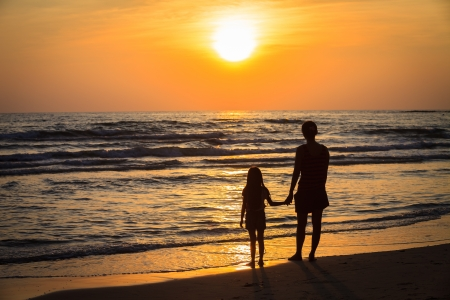 Mother and her daughter silhouettes on beach at sunset photo