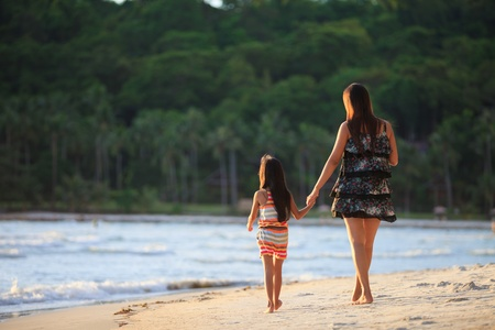 Mother and daughter walking on the beach photo