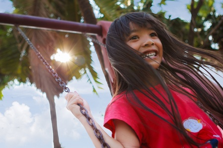 climbing frames: Smiling little girl enjoys playing in a children playground