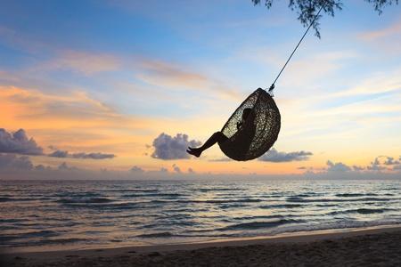 columpio: Silueta jugando swing en la playa