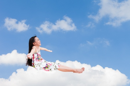 daydreaming: Smiling little girl sitting on the cloud over sky