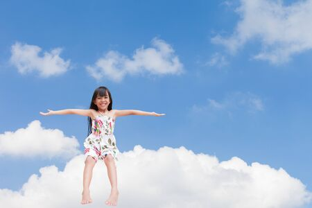 Smiling little girl sitting on the cloud over sky photo