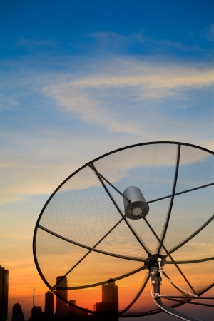 Black antenna satellite dish over twilight sky after sunset in cityscape photo
