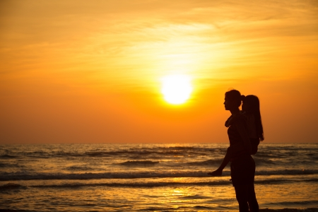 ashore: Silhouette mother with daughter ashore on sunset
