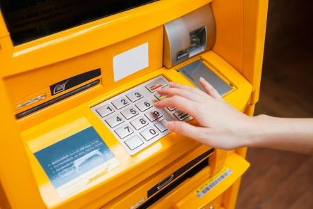 Vinger die op wachtwoord nummer op geldautomaat