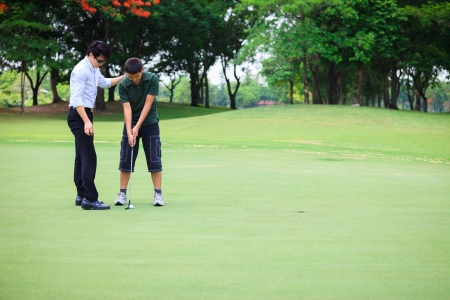 Professional teaching teenager boy to play golf photo