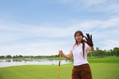 Young girl golfer show golf ball photo