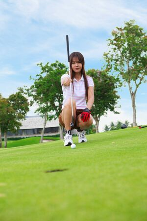 Golfer young woman lining up a putt on the green photo