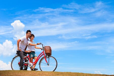 Beautiful Couple on bicycle with nice blue sky photo