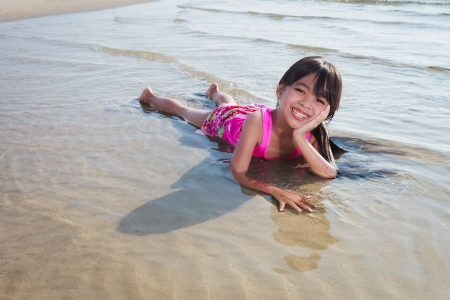 Smiling little girl laying in water on the beach