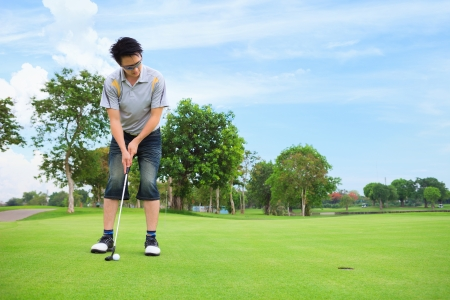 Young golfer putting on green photo