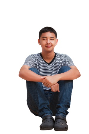 Smiling asian teenager boy sitting, Isolated on white photo