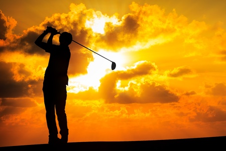 Silhouette golfer at sunset